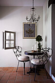 Small round table with nostalgic metal chairs in the corner of a country house