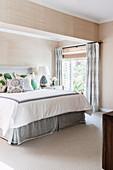 Double bed in bright bedroom with beige wallpaper