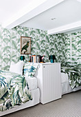 Single beds and wallpaper with leaf motif in the bedroom