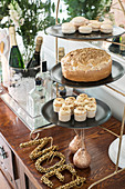 Christmas buffet of cake and pastries on cake stand next to tray of drinks