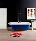 Blue, free-standing bathtub against a black wall, paper butterflies as wall decoration