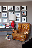 Vintage leather armchair and console table with table lamp and books against gray wall with photo gallery