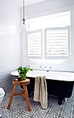 Freestanding bathtub under the louvre window in the small bathroom