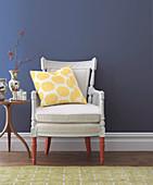 Alter weißer Sessel mit rotbraunen Beinen vor blauer Wand