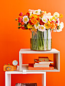 Bouquet of poppies on shelf modules against orange wall