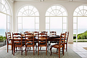 Long table with wooden chairs in front of arched window fronts with sea view
