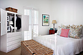 White bedroom with metal bed, wicker chest and open closet