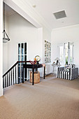 Hallway area with black and white striped armchair and stairway in beach house