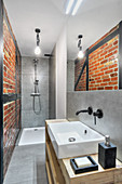 Shower, washstand and exposed brickwork in narrow bathroom