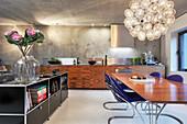 Blaue Designerstühle am Esstisch in moderner offener Wohnküche