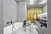 Grey, modern bathroom with indirect lighting on mirrored wall