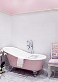 Freestanding pink bathtub in bathroom with historical flair