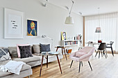 Pale grey sofa, coffee table and pink armchair in front of dining area in bright, open-plan interior