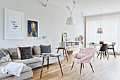 Hellgraues Polstersofa, Coffeetable und rosa Sessel, im Hintergrund Essbereich in hellem, offenem Wohnraum