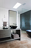 Modern vanity in the bathroom in dark natural tones with stone floor