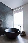 Freestanding oval bathtub against a shimmering mosaic wall