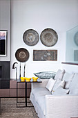 Wall plates and ethnic decorations in the living room in shades of gray