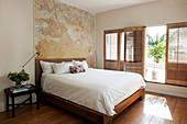 Bett vor ungestrichener Wand mit Patina im Schlafzimmer
