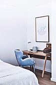 Narrow wooden wall table for the home office with light blue velvet chair in the corner of the bedroom