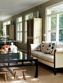 Light upholstered sofa with pillows and dark coffee table
