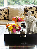 Pillows on sofa, pots with bouquets of flowers and statue on wooden tray in foreground