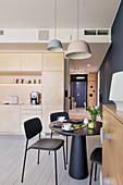 Black dining set in modern interior with open-plan kitchen