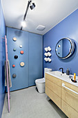 Modern bathroom with blue walls and fitted cupboards with hooks on door