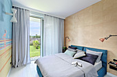 Wall clad in plywood panels in summery bedroom