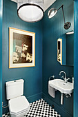 Sink and toilet in bathroom with dark blue walls