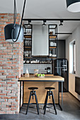 Open-plan kitchen with suspended shelves and breakfast bar next to brick wall
