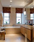 Classic, beige bathroom with twin washstand and bathtub