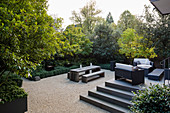 Lounge furniture on terrace in luxurious garden with gravel floor