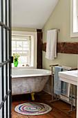 Old, free-standing bathtub in rustic bathroom with wooden beams