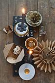 Weihnachtliche Tischdeko mit goldenem Porzellan, Papierblumen, Stern und grauen Kerzen auf Schieferplatte