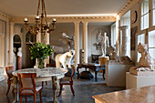 Entrance hall filled with a taxidermy polar bear, regency chairs, marble topped table and large plaster casts