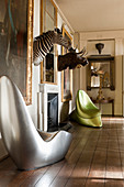 Silver seat and green satin acrylic seat in room with mounted moose and zebra heads