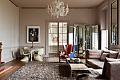 Murano chandelier in drawing room with classic chairs and a union jack upholstered winged back armchair