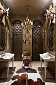 Cloakroom with french porcelain hand basins, padded leather doors, antlers and cow hide rug