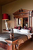 Grand mahogany bed with mirrored headboard in bedroom with red lampshades