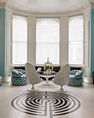 Seating, round table and labyrinth pattern on floor in white and sky-blue interior with bay window