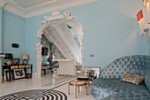 Sofa in sky-blue interior with arched doorway decorated with stucco elements