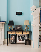 Console table against sky-blue wall next to open doorway with contemporary stucco ornamentation