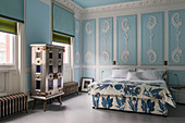 Bedroom with sky-blue walls and ornate stucco elements
