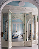 Tall wardrobe with mirrored doors in sky-blue bedroom with ornate stucco elements