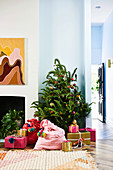 Living room decorated with Christmas tree, colorful Santa bags and wrapped presents