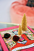 Sunglasses and golden mini fir trees on art book