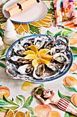 Austern mit Zitronen auf farbenfroh weihnachtlich gedecktem Tisch