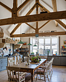 Wooden table in large, country-house-style kitchen-dining room with exposed roof structure