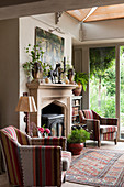 Two striped armchairs flanking fireplace in renovated English country house