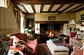 Inglenook fireplace and wood-beamed ceiling in living room of English country house
